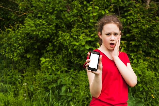公園に立っている間空白の画面の携帯電話を示すショックを受けた美少女 無料写真