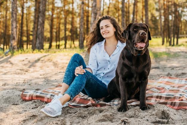 彼女の犬と一緒にピクニックをしている若い女性 無料写真