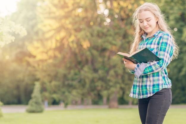公園で本を勉強している少女 無料写真
