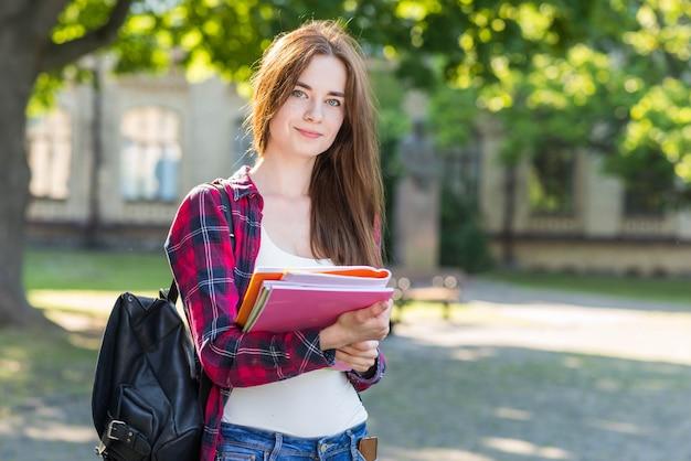 公園で本を持つ女子高生の肖像画 無料写真