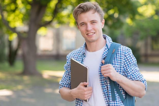 公園で本を持つ学校少年 無料写真