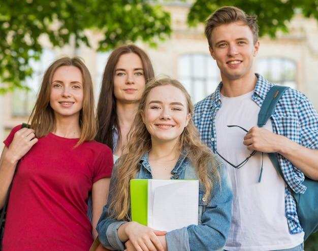 Группа молодых студентов перед зданием школы Бесплатные Фотографии