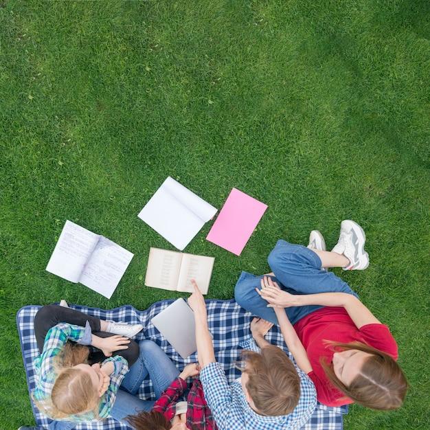 草の上の本を持つ学生のトップビュー 無料写真