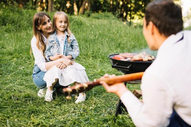 自然の中でバーベキューをしている家族 無料写真