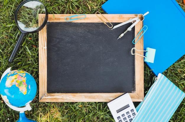 文房具とチョークボードは緑の芝生に設定 無料写真
