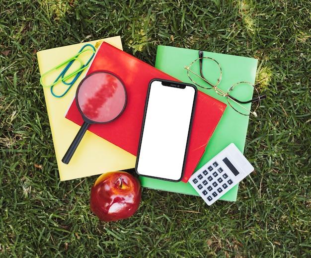 光学ツール、リンゴ、草の上のデバイスを備えたノートブック 無料写真
