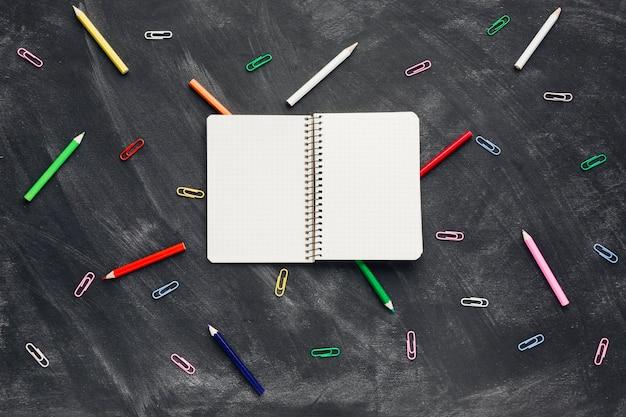 Открыл блокнот рядом с карандашами и скрепками Бесплатные Фотографии