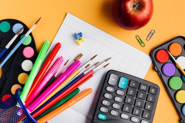 Разноцветные школьные принадлежности и красное яблоко на желтом столе Бесплатные Фотографии