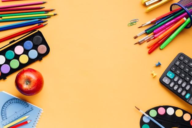 Школьные принадлежности разбросаны на желтом столе Бесплатные Фотографии