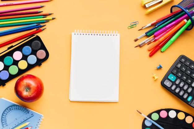 黄色の机の上の空白のメモ帳の周りに散らばって多色学校文房具 無料写真