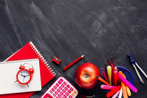 真っ赤な学用品と黒板にアップル 無料写真