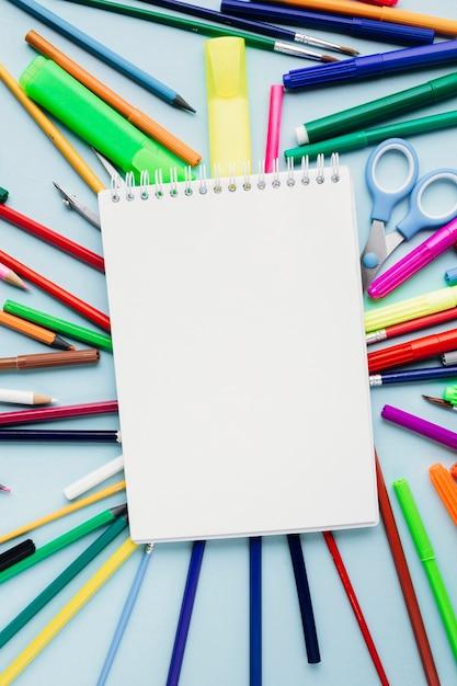 青の背景にカラフルな文房具の新しいノートをクリア 無料写真