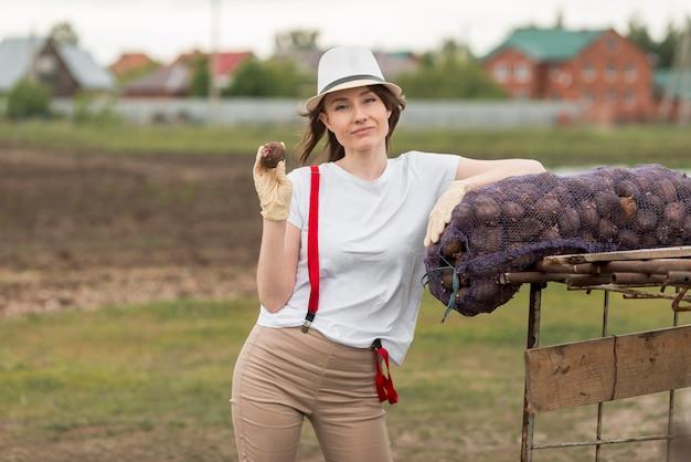 農場で果物の袋を持つ女性 無料写真