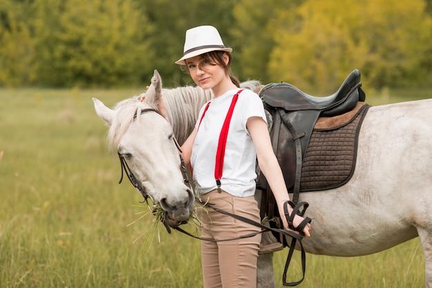 田舎で馬と一緒に歩いている女性 無料写真