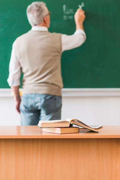 数学の先生が本を持つテーブルの近くの黒板に書く 無料写真