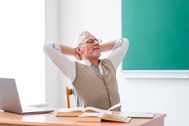頭の後ろに手を持つ教室に座っている先輩教授 無料写真