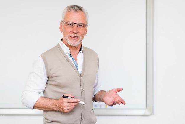 マーカーボードの近くに立ちながら説明する先輩教授 無料写真
