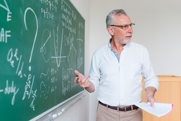 教室での式を説明する高齢の数学教師 無料写真