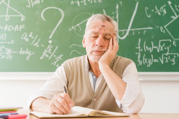 Уставший пожилой учитель математики спит за столом Бесплатные Фотографии