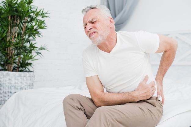 背中の痛みを持つ老人 無料写真