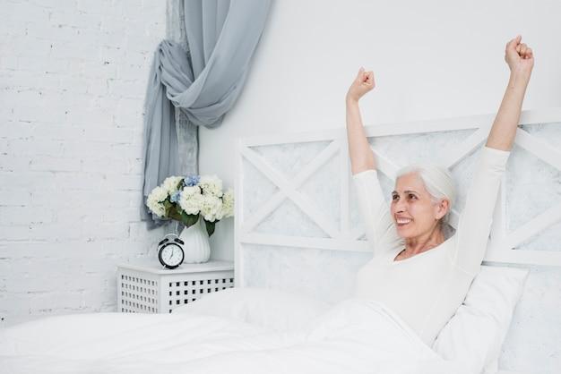 年配の女性がベッドで目を覚ます 無料写真
