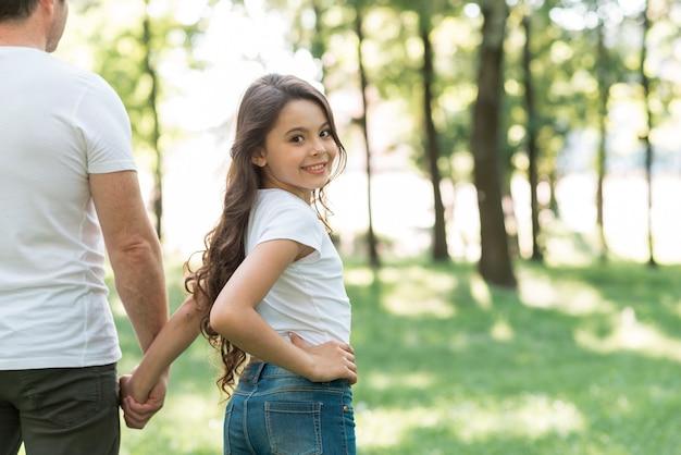彼女の父親と一緒に公園を歩きながらカメラ目線微笑んでいる女の子 無料写真