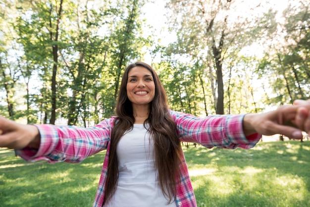 公園で彼女のパートナーの手を引いて笑顔の女性 無料写真