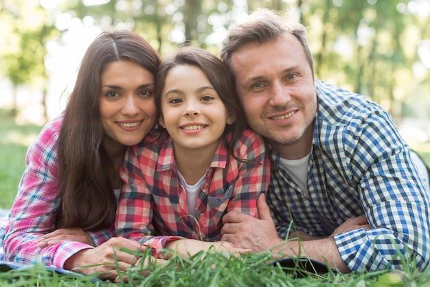 草の上に横になっている笑顔の家族のクローズアップ 無料写真