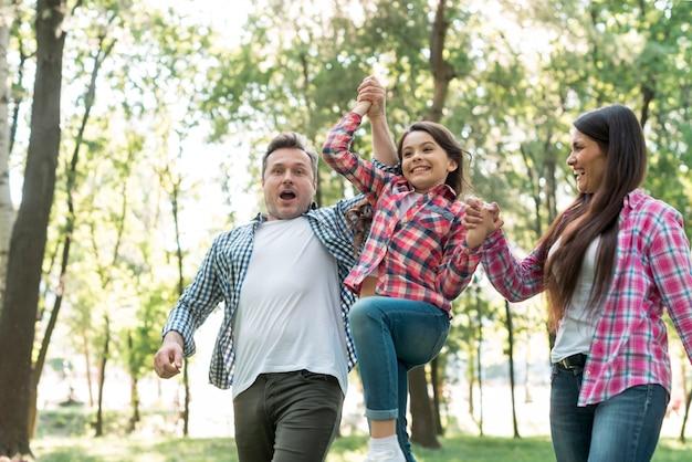公園で娘を持ち上げる親 無料写真