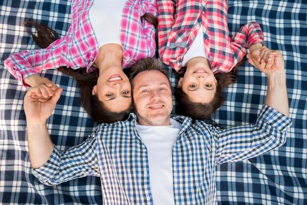 青い毛布の上に横たわる幸せな家族のトップビュー 無料写真