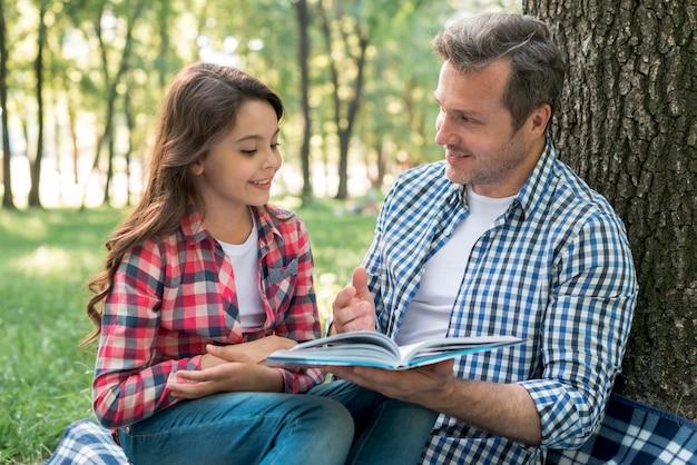 父は公園に座っている彼の娘に物語を語っています 無料写真