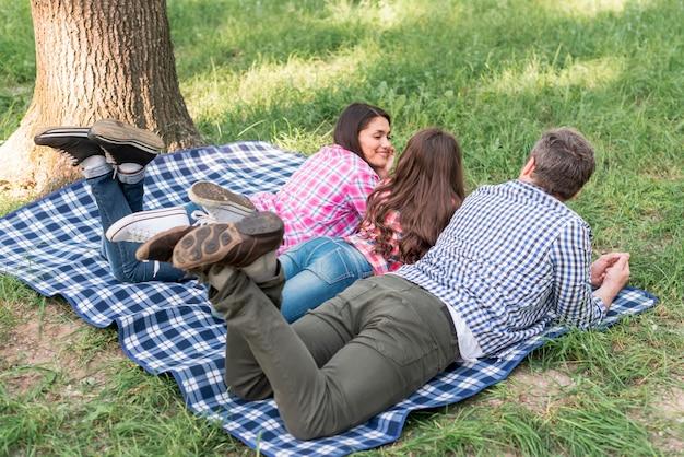 家族の庭の芝生の上青い市松模様の毛布の上に横たわる 無料写真