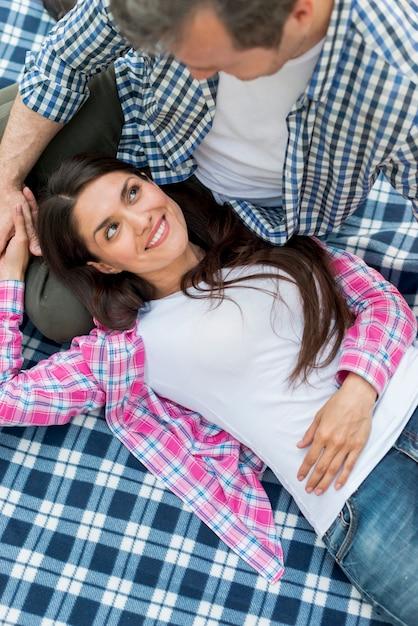 お互いを見て男の膝の上に横たわる幸せな女 無料写真