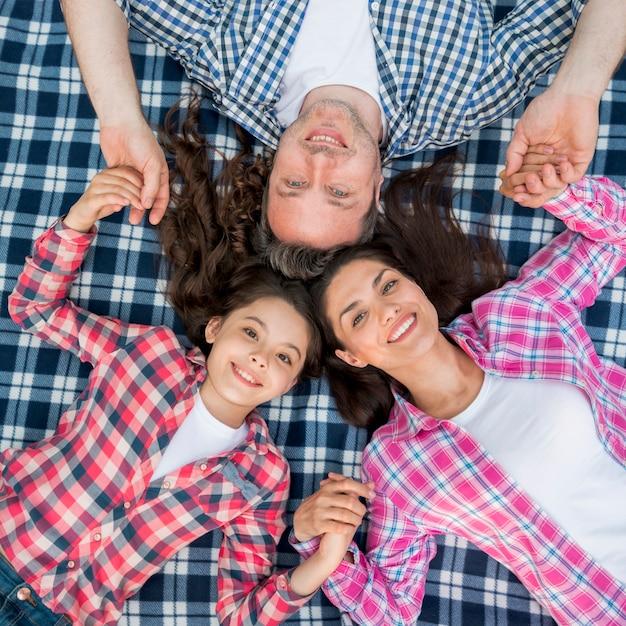 市松模様の毛布の上に横になっている笑顔の家族の立面図 無料写真