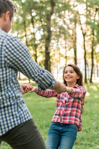 彼女の父親と公園で遊んでかなり微笑の女の子 無料写真