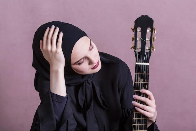イスラム教徒の女性がギターを弾いて 無料写真