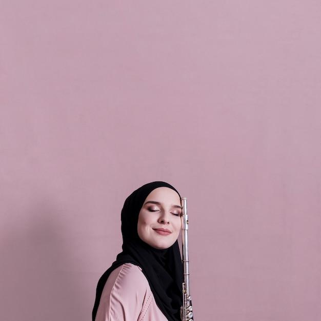 フルートで遊ぶイスラム教徒の女性 無料写真