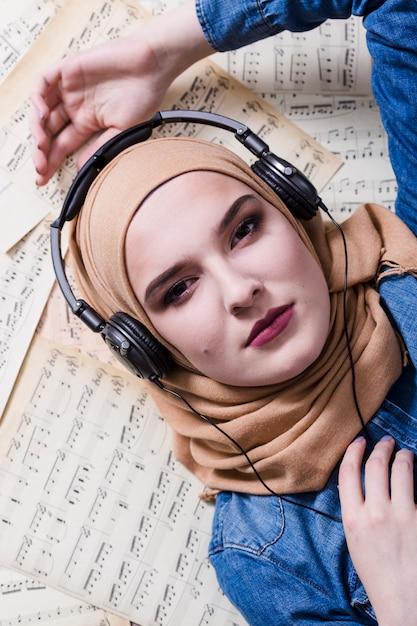 イスラム教徒の女性がヘッドフォンで音楽を聴く 無料写真
