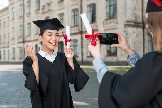 卒業時にお互いの写真を撮る学生 無料写真