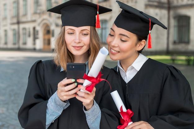 スマートフォンを見ている学生と卒業の概念 無料写真