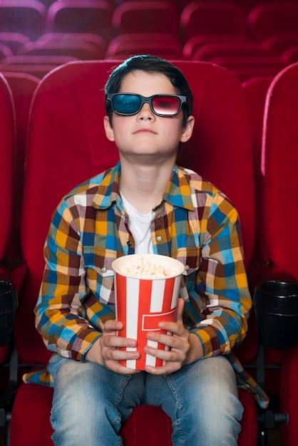 映画館で映画を見ている少年 無料写真