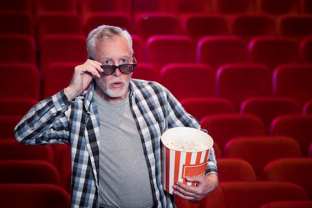 映画館で映画を見ている老人 無料写真