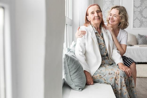 Портрет внучки и бабушки, сидя на подоконнике у себя дома Бесплатные Фотографии