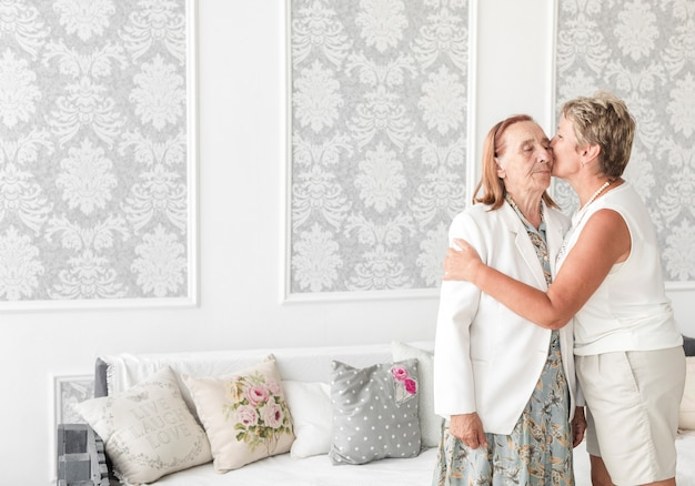 Зрелая женщина целует ее старшую мать дома Бесплатные Фотографии