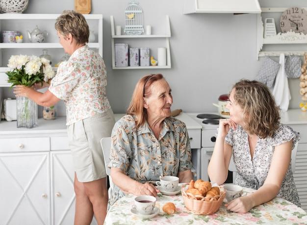 朝食をとりながらおばあちゃんと壮大な娘がお互いに話して 無料写真