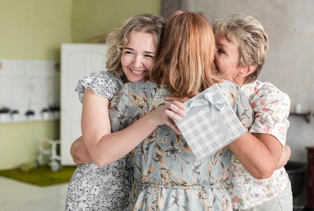 ギフト用の箱を押しながらおばあちゃんを抱き締める母と娘の笑顔 無料写真