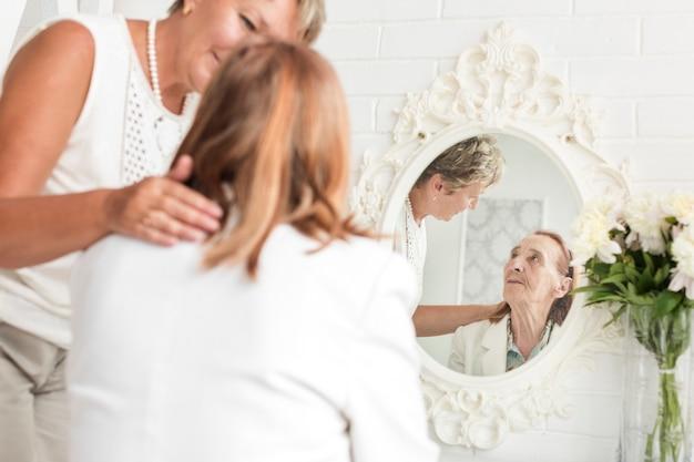 熟女の鏡の前に座っている彼女の母親を見て 無料写真