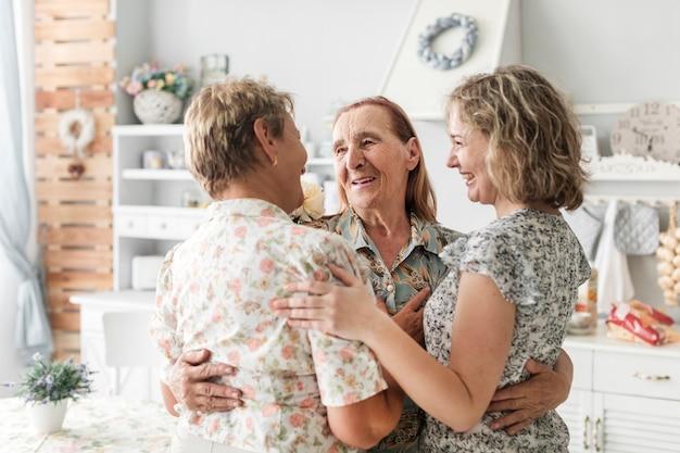 Обнимать улыбающихся много поколений женщин дома Бесплатные Фотографии