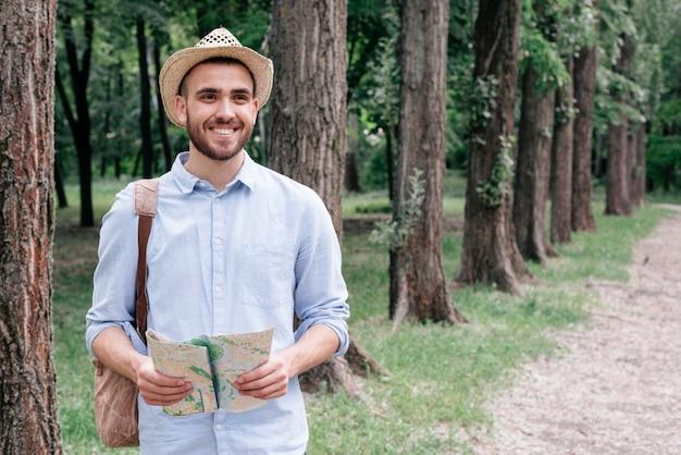 公園で地図を持って帽子をかぶっている若い男の笑みを浮かべてください。 無料写真
