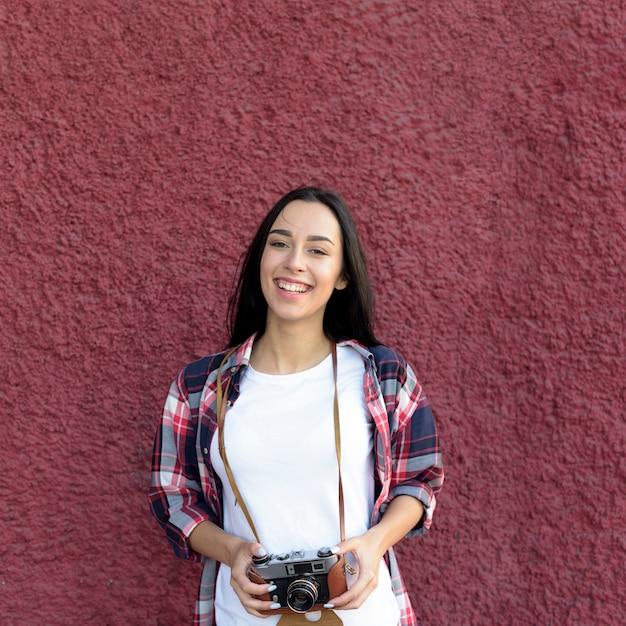 あずき色の壁に対してカメラ立って保持している笑顔の女性の肖像画 無料写真